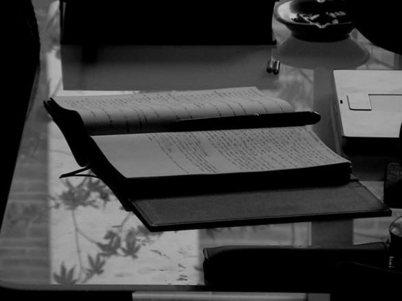 Cuaderno, pluma y mesa de poliuretano en gris. Fotografía de Olmo Z. de la serie Textos. 2015